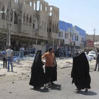 Residents gather at the scene of a car bomb attack in Baghdad on Saturday, when a series of bombings in the capital left 22 people dead, police and medics said. A suicide blast at a police checkpoint Tuesday left another 23 people dead. | REUTERS