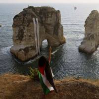 A protester wearing a Palestinian flag throws flowers into the Mediterranean during a demonstration against Israel's military action in Gaza, at Rawshe rock in Beirut on Tuesday. Israel pounded targets across the Gaza Strip the same day, saying no ceasefire was near as top U.S. and United Nations diplomats pursued talks on halting the fighting that has claimed more than 600 lives. Hamas, the dominant group in the Gaza Strip, and its allies fired more rockets into Israel, triggering sirens in Tel Aviv. One hit a town on the fringes of Ben-Gurion International Airport, lightly injuring two people, officials said. Banners with the names of Palestinians killed in Gaza, hung up by the protesters, are seen on Rawshe rock. | REUTERS