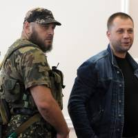 Self-proclaimed Prime Minister of the pro-Russian separatist 'Donetsk People's Republic' Alexander Borodai (right) stands next to a security serviceman during a press conference in the eastern Ukrainian city of Donetsk on Sunday. Pro-Russian rebels said they had recovered objects which appear to be the black boxes of downed Malaysian airliner MH17, and announced they are willing to hand them over to international investigators. | AFP-JIJI