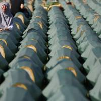 A Muslim woman cries near the casket of her relative in the village of Kozarac, Bosnia, before a reburial of 284 newly identified bodies that were put to rest in several local cemeteries Sunday. The majority of the 284 bodies were excavated from a mass grave in the village of Tomasica in 2013 and identified as those belonging to Bosnian non-Serbs that went missing in 1992, only to be found buried in several mass grave locations years after the war ended. | AP
