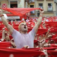 Participants hold red scarves on Sunday as they celebrate the noon launch of 'Chupinazo' firecrackers, marking the start of the San Fermin Festival in front of the town hall in Pamplona, northern Spain. | AFP-JIJI