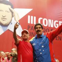 Venezuelan President Nicolas Maduro (right) embraces retired Gen. Hugo Carvajal as they attend the Socialist party congress in Caracas in this picture provided by Miraflores Palace on Sunday, after the ex-military intelligence chief flew home from detention in Aruba.