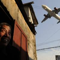A man watches an airliner passing over his house and on toward Hongqiao international airport in Shanghai in January 2012. | AFP
