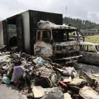 Debris is seen next to burned-out vehicles after an explosion and fire following a traffic accident at a section of the Hukun highway in Shaoyang, Hunan province, on Saturday. At least 38 people were killed in the collision between a bus and a van carrying flammable liquids in southern China, state media reported. | REUTERS