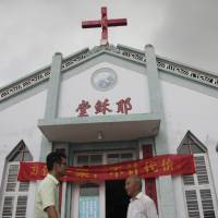 Pastor Tao Chongyin (left) speaks with church member Fan Liang'an in front of Wuxi Christian Church on July 15. Behind them, Chinese characters for 'Church of Jesus' have been erected on the church in Wenzhou in eastern China's Zhejiang province . | AP