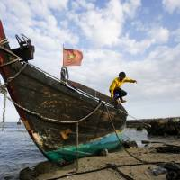 A fisherman jumps from his damaged fishing boat on the island of Ly Son, in Vietnam's central Quang Ngai province, on July 1. | REUTERS