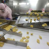 Chicken nuggets roll down a conveyor belt in front of workers at Shanghai Husi Food Co. in Shanghai on Sunday. Shanghai city officials have shut a the Shanghai Husi factory for selling out-of-date meat to restaurant chains including McDonald's, KFC and others, authorities said Monday in China's latest food safety scandal.   AFP