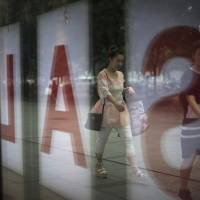 Women walk past a fashion outlet offering a summer sale at a shopping mall in Beijing on Wednesday. China's economic growth edged up in the latest quarter and more than 7 million new jobs were created in the first half of the year, easing pressure on communist leaders as they try to prevent a precipitous slowdown in the world's second-largest economy. | AP