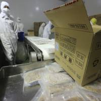 Employees work on a production line prior to a raid by officers from the Shanghai Food and Drug Administration at the Husi Food factory in Shanghai on July 20. | REUTERS
