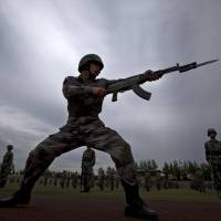 A Chinese People's Liberation Army cadet conducts a bayonet drill at the PLA's Armored Forces Engineering Academy Base, on the outskirts of Beijing on Tuesday.   AP