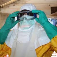 A member of Doctors Without Borders puts on protective gear in the isolation ward of the Donka Hospital, where people infected with the Ebola virus are being treated, Saturday in Conakry, Guinea. | AFP-JIJI