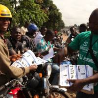 A Samaritan's Purse team member hands out pamphlets to educate the public on the Ebola virus in Monrovia,  An isolation unit for Ebola victims in Liberia's capital is overrun with cases and health workers are being forced to treat up to 20 new patients in their homes, government officials said Tuesday. | REUTERS