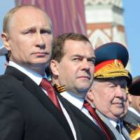 Russia's President Vladimir Putin (left) and Prime Minister Dmitry Medvedev (second from left) attend a Victory Day parade at Red Square in Moscow on May 9, amid tensions in Ukraine following Moscow's annexation of Crimea. | AFP