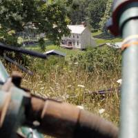 A farmhouse is framed by pipes connecting pumps during hydraulic fracturing work to release natural gas from the Marcellus Shale field at a Range Resources site in Claysville, Pennsylvania, in July 2011. | AP