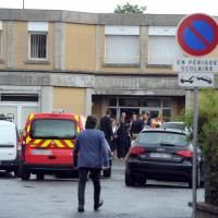 Policemen and firemen stand guard in front of the primary school Edouard-Herriot, where a female teacher was stabbed to death in front of her pupils by a student's mother, on Friday in the southern French town of Albi. | AFP-JIJI