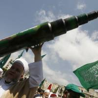 A man holds a mock Qassam rocket Friday in Sidon at a rally organized by Lebanese and Palestinian supporters of the Islamist movement Hamas and the Islamic Group Jamaa Islamiya, in solidarity with Palestinians in the Gaza strip, where Hamas is engaged in a major confrontation with the Israeli army. | AFP-JIJI
