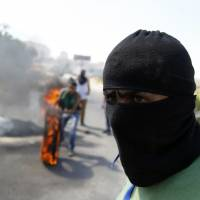Palestinians block the road to the entrance of Israeli-run Ofer prison in the West Bank village of Betunia with burning tires during clashes with Israeli soldiers on Friday. | AFP