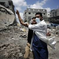 A medic helps a Palestinian in the Shijaiyah neighborhood, which was heavily shelled by Israel during fighting, in Gaza City on Sunday. At least 50 Palestinians were killed by Israeli shelling the same day in the Gaza neighborhood, where bodies were strewn in the street and thousands fled for shelter to a hospital packed with wounded, witnesses and health officials said. | REUTERS