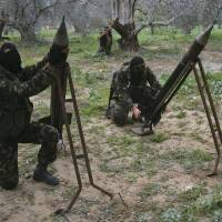 Masked Palestinian militants from Islamic Jihad place homemade rockets before later firing them into Israel on the outskirts of Gaza City, in the Gaza Strip, in December 2008.   AP
