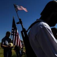 A man bows his head in prayer with about 250 gun-rights advocates before participating in an 'open-carry' demonstration during the Independence Day parade in Westcliffe, Colorado, on Friday. | AP