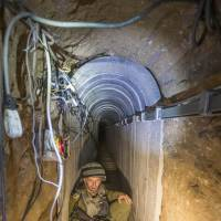 An Israeli officer gives journalists a tour of a tunnel dug by Palestinian militants at the Israel-Gaza border on July 25. The network of tunnels, dubbed 'lower Gaza' by the Israeli military, is taking center stage in the latest war between the two sides. | AP