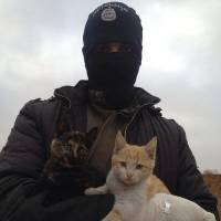 An image from Twitter purportedly shows an Islamic State militant. The winter clothing suggests the photo predates the current offensive in Iraq. | @ISILCATS