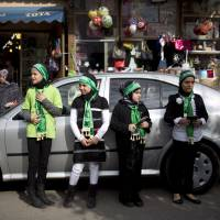 Israeli Arab girls look for passing cars while handing out Muslim prayer books in the main street of Tayibe, an Arab town in central Israel, in January. | AP