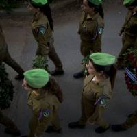 Israeli soldiers carry wreaths to be placed on the grave of 2nd Lt. Roy Peles, during his funeral at Kiryat Shaul military cemetery in Tel Aviv on Sunday. Peles, a 21-year-old infantry officer, was killed on Saturday during fighting in the Gaza Strip. | AP
