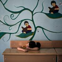A Palestinian girl rests Monday in a classroom at the New Gaza Boys United Nations school, where dozens of families have sought refuge after fleeing in fear of Israeli airstrikes. | AP