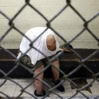 The nation's 3,300 local jails have turned into makeshift treatment centers for people with serious mental illnesses. Most are arrested for nonviolent crimes, such as this U.S. veteran, pictured in a holding pen at Chicago's Cook Country Jail after being picked up on a narcotics charge on June 26. | AP