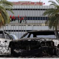 Burnt vehicles are seen in the compound of Tripoli international airport Monday following fighting between rival armed groups the previous day. Islamist militias attacked the rival Zintan group that controls the airport, triggering fierce clashes that halted flights, officials said. | AFP-JIJI
