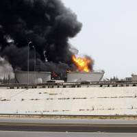 A fuel depot burns Monday near the airport road in Tripoli. Libyan forces on Tuesday battled Islamist militants with rockets and warplanes for control of an army base in Benghazi after at least 30 people were killed in overnight fighting. A rocket hit the fuel depot two days ago.   REUTERS