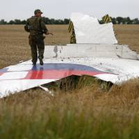 An armed pro-Russian separatist stands on part of the wreckage of the crashed Malaysia Airlines Boeing 777 plane in Ukraine's Donetsk region Thursday. | REUTERS