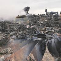 An emergency worker inspects the site of a Malaysia Airlines Boeing 777 plane crash in Ukraine on Thursday.  | REUTERS