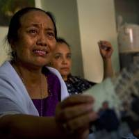 Grieving Indonesian Yuriah Tanzil (left), sister of Ninik Yuriani, a passenger on doomed Malaysia Airlines Flight MH17, holds up a photograph of her sister at the family residence in Jakarta on Friday after the plane was shot down in eastern Ukraine a day earlier. | AFP