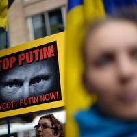 Members of the Australian-Ukrainian community hold placards showing Russian President Vladimir Putin during a protest rally in Sydney on Saturday. Demonstrators demanded that Putin be barred from entering Australia for G-20 leaders summit in November. | AFP
