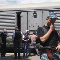 As a pro-Russian separatist holds his nose, monitors from the Organization for Security and Cooperation in Europe stand by a refrigerated wagon containing the bodies of passengers from the crashed Malaysia Airlines plane at a railway station in the town of Torez, in eastern Ukraine's Donetsk region, on Sunday. | REUTERS