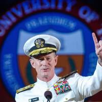 U.S. Navy Adm. William McRaven, an alumnus, does the Longhorns' 'Hook 'em Horns' hand signal during his commencement keynote address at the University of Texas in Austin in May. The University of Texas System regents on Tuesday selected McRaven as the lone finalist for the job of chancellor, overseeing the system's 15 campuses and $14 billion budget. | AP