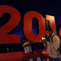 Aram Barra of Mexico holds a candle as people gather in Melbourne on Friday, after news broke that downed Malaysia Airlines flight MH17 was carrying many participants headed to the 20th International AIDS Conference planned for this weekend in the city. | AFP