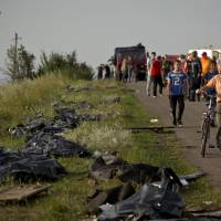 Bodies of victims are placed in plastic sacks by the side of the road at the crash site of Malaysia Airlines Flight 17 near the village of Hrabove, eastern Ukraine, on Saturday. | AP