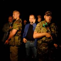 Alexander Borodai (center), the self-proclaimed leader of the separatist, pro-Russian 'Donetsk People's Republic,' arrives at the site of the crash of a Malaysian airliner carrying 298 people, near the town of Shaktarsk in rebel-held east Ukraine on Thursday. The plane was shot down by a surface-to-air missile Thursday but it was unclear who fired the weapon. | AFP