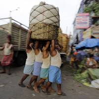 Indian laborers carry vegetables at a wholesale market in Kolkata on Wednesday. | AP