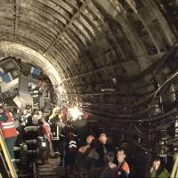 Rescue teams work inside a Moscow subway tunnel Tuesday after a train derailed, claiming at least 20 lives. Workers were seen trying to force open the mangled doors of a car to get at more bosies. The cause of the derailment is being investigated. | AP