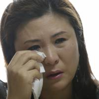 Former North Korean spy Won Jeong-hwa wipes away a tear during an interview at her apartment in April. | AP