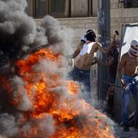 Masked Palestinian protesters throw stones toward Israeli police during clashes in the Shuafat neighborhood in Israeli-annexed Arab East Jerusalem, on Wednesday, after a Palestinian teenager was kidnapped and killed in an apparent act of revenge for the murder of three Israeli youths. | AFP-JIJI