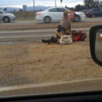 An amateur video provided by motorist David Diaz shows a California Highway Patrol officer straddling a woman and punching her in the head at the side of Interstate 10, west of downtown Los Angeles. | AP