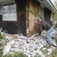 Chad Devereaux examines bricks that fell from his in-laws' home in Sparks, Oklahoma, on Nov, 6, 2011, after two earthquakes struck the area in less than 24 hours. | AP