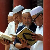 Chinese Muslims read the Quran at a mosque in Tancheng, Shandong province, on June 30 — the start of Ramadan. | AFP-JIJI