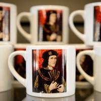 Souvenir coffee mugs showing King Richard III are displayed Thursday at the new visitor center on the site where his remains were discovered in Leicester, central England. | AFP