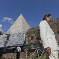 Japanese businessman Yuzo Yagi, from Osaka, stands in front of the monument Pyramid of Cestius, in Rome, Tuesday, Yagi is funding the restoration project of this ancient tomb, which was built for Roman magistrate Gaius Cestius between 18 and 12 B.C. in the shape of a pyramid, a fashion common after Rome conquered Egypt in 31 B.C. | AP